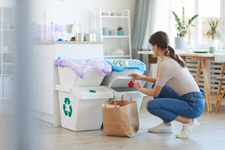 Photo pour Young woman sorting plastic and paper into the different bins in the kitchen at home - image libre de droit