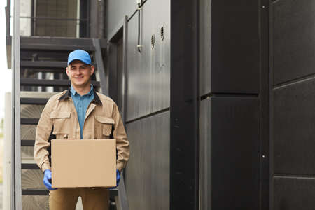 Foto für Portrait of young delivery person in uniform holding parcel and smiling at camera outdoors - Lizenzfreies Bild
