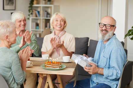 Photo pour Portrait of senior bearded man holding gift box and smiling at camera while his friends congratulating him at the table - image libre de droit