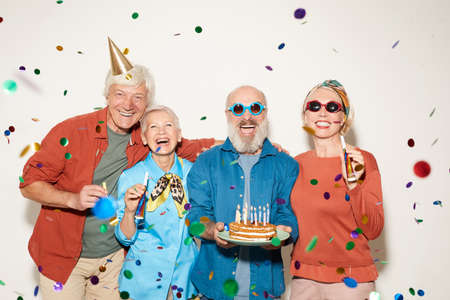 Photo pour Portrait of group of senior people with birthday cake standing under the confetti and smiling at camera against the white background - image libre de droit