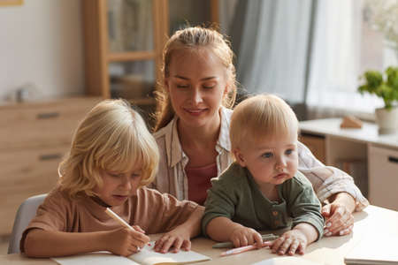 Photo for Young mother sitting at the table with baby and helping to her elder son with homework - Royalty Free Image