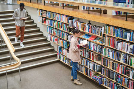 Photo pour Young people choosing books and reading them in the library - image libre de droit
