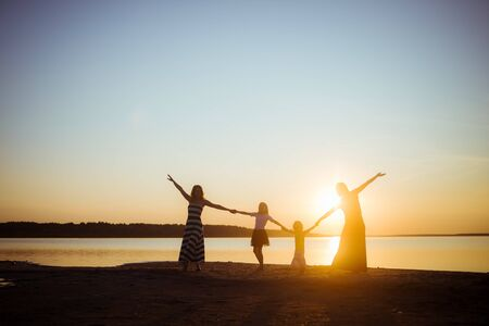 Foto de Silhouette of people holding hands with each other on sunset light background. Good mood and pastime among the younger and older generation. Friendship and freedom. Beautiful landscape. - Imagen libre de derechos