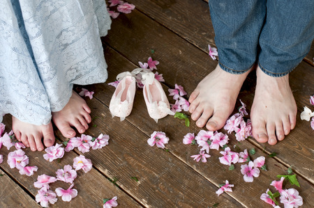 Family feet with baby's bootees on wooden brown boards among flowers. Birth expectation concept.