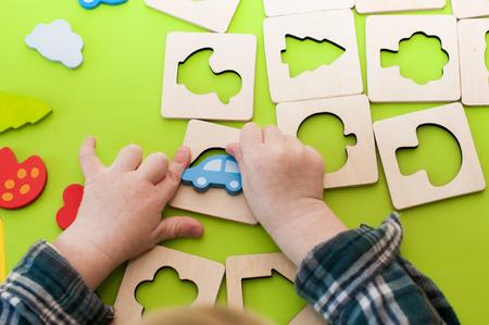 children's hands playing with wooden shape sorter indoor.
