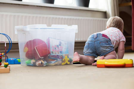 Photo for Baby playing alone with toys on a carpet on the floor at home - Royalty Free Image