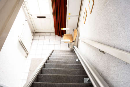 Photo for Automatic stair lift on staircase taking elderly people and disabled persons up and down in a house close-up - Royalty Free Image