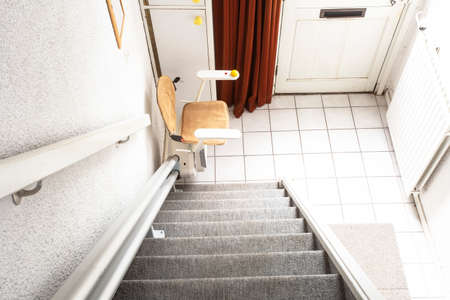 Photo for Automatic stair lift on staircase taking elderly people and disabled persons up and down in a house - Royalty Free Image