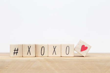 Foto de Wooden cubes with hashtag and XOXO hugs and kisses letters of love near white background, social media concept - Imagen libre de derechos