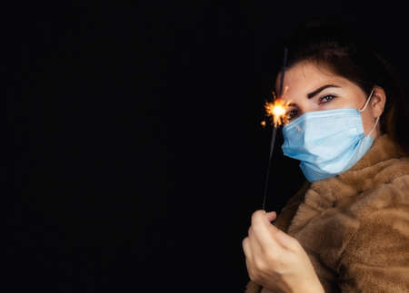 Photo for Happy new year, portrait of a young woman wearing medical mask and holding sparklers light in the dark for Covid-19, Coronavirus and New year concept - Royalty Free Image