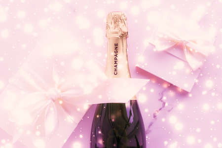 Photo pour Celebration, drinks and branding concept - Champagne bottle and gift box on pink holiday glitter, New Years, Christmas, Valentines Day, winter present and luxury product packaging for beverage brand - image libre de droit