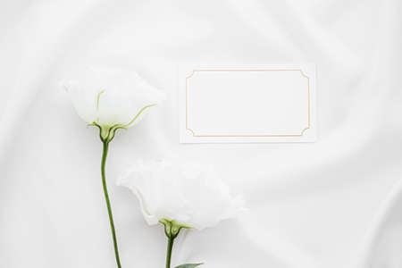 Photo pour Wedding invitation or gift card and white rose flowers on silk fabric as bridal flatlay background, blank paper and holiday branding, flat lay design - image libre de droit