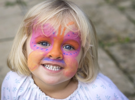 A 4 year old girl smiling at the camera with a butterfly painted over her face