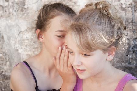 Two teenage girls whispering secrets