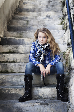 A teenager wtih attitude in cool funky clothes with high boots sitting on stairs, looking confused