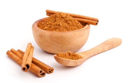 powder of cinnamon in wooden bowl with spoon andCinnamon sticks