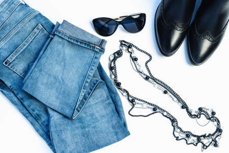 Overhead view of womans casual outfit on white background - glasses, blue jeans, necklace and leather chelsea boots. Flat lay, top view, copy space. Trendy, minimal hipster look.の素材 [FY310134967766]