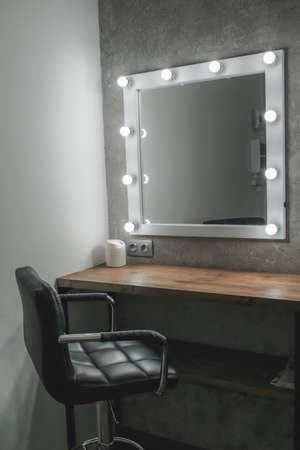 Foto de Interior of a beauty salon. Room with makeup mirror lights and black chair - Imagen libre de derechos