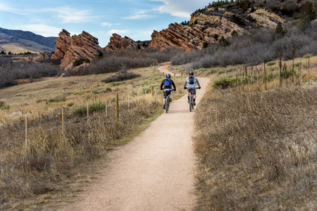 Two cyclists ride mountain bikes side by side up a beautiful, dirt bike trail leading to red rocks on a sunny summer or autumn day in search of recreation and adventure.