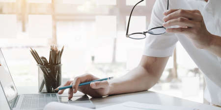 Photo pour Businessman using laptop computer and holding glasses. - image libre de droit