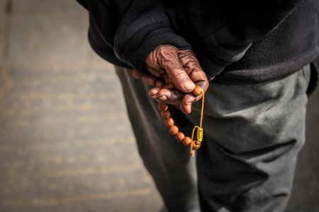 Hand of an old man holding beads