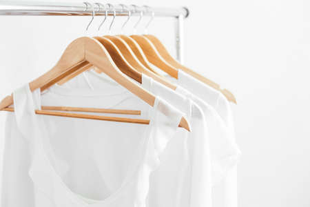 Photo pour Wooden hangers with white blouses on the counter. - image libre de droit
