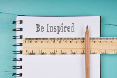 Be Inspired word on notebook, wooden ruler and pencil on blue wooden background. Top view. Business concept.