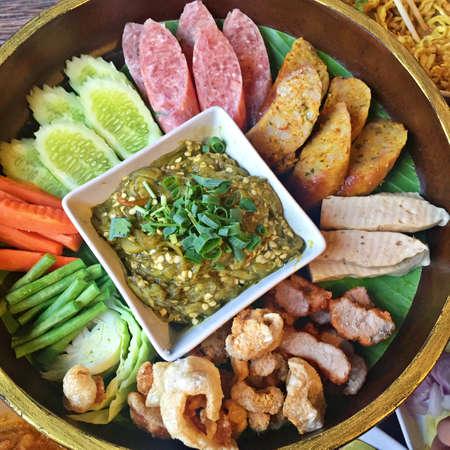 Photo pour Khan tok or Khantoke, Thai food traditionally dinner include Green chilli dip, boiled vegetables, Thai spicy sausage, sour pork and Crispy Pork Skin - image libre de droit