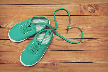 Top view of a pair of shoes with laces making heart shape on wooden floor. Heart made of shoelaces