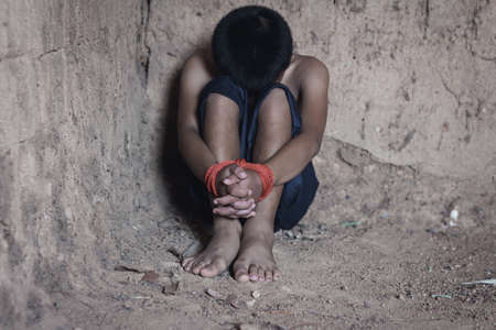 Kidnapped little boy tied with rope.Abused and tortured concept. Human trafficking concept.Stop abusing violence.