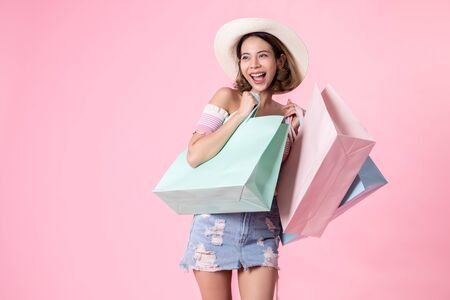 Photo pour Asian pretty young woman walking over pink  pastel background. She smiling and  holding shopping bags. she nice-looking lovely attractive shine She holding mobile. - image libre de droit