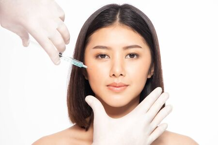 Photo pour Asian young woman gets injection of in her lips. Woman in beauty salon. plastic surgery clinic. Beautiful woman gets injection in her face. - image libre de droit