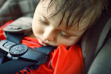 Foto de Closeup portrait of a cute adorable little boy toddler tired and sleeping belted in carseat on his trip, safety protection concept - Imagen libre de derechos