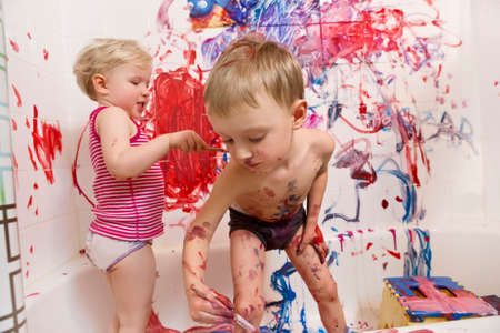 Foto de Portrait of two cute adorable white Caucasian little boy and girl playing painting on walls  in bathroom, having fun, lifestyle active childhood concept, early education development - Imagen libre de derechos
