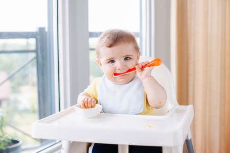 Photo pour Portrait of cute adorable Caucasian child boy with dirty messy face sitting in high chair eating apple puree with spoon. Everyday home childhood lifestyle. Infant trying supplementary baby food - image libre de droit