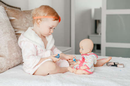 Adorable cute blonde Caucasian baby girl painting nails for her doll sitting on bed at home. Female child doing manicure for her toy. Toddler playing using cosmetics.