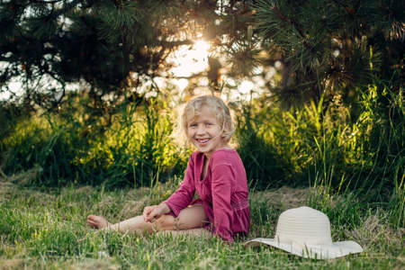 Foto de Portrait of cute beautiful blonde Caucasian girl in red pink dress with messy untidy hair sitting on ground grass in park outdoor at sunset. Happy adorable barefoot child kid enjoying summertime. - Imagen libre de derechos