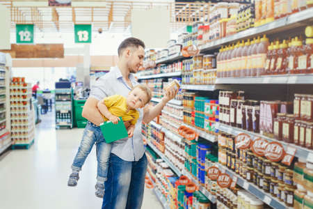 Caucasian father dad in grocery store shopping buying food and holding carrying baby son under arm. Man parent with toddler kid choosing meal for dinner lunch. Difficult parenting authentic moment.