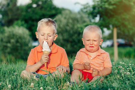 Photo pour Two Caucasian funny children boys siblings sitting together eating sharing one ice-cream. Toddler younger baby crying and older brother teasing him. Love envy jealous brothers friendship. - image libre de droit
