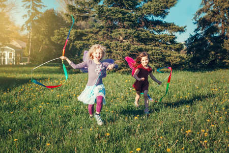 Photo pour Happy children girls playing with ribbons in park. Cute adorable kids running on meadow playing together. Outdoor summer backyard activity for kids. Happy childhood candid authentic lifestyle. - image libre de droit