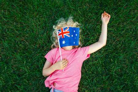 Photo for Adorable cute happy Caucasian girl holding Australian flag. Funny child kid covering her face with Australia flag. Little citizen celebrating Australia Day holiday in January outdoor. - Royalty Free Image