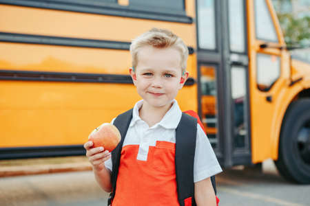 Photo pour Caucasian boy student with backpack near yellow bus on first September day. Child kid eating apple fruit at school yard outdoor. Education and back to school in Autumn Fall. - image libre de droit