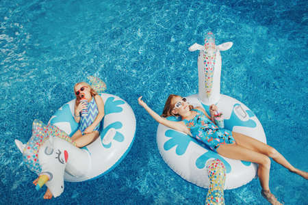 Photo pour Cute adorable girls sisters friends with drinks lying on inflatable rings unicorns. Kids children siblings in sunglasses having fun in swimming pool. Summer outdoor water activity for kids. - image libre de droit