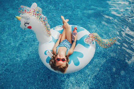 Photo pour Cute adorable girl in sunglasses with drink lying on inflatable ring unicorn. Kid child enjoying having fun in swimming pool. Summer outdoor water activity for kids. View from above overhead. - image libre de droit