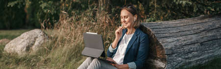 Foto de Woman working on laptop in park o . Student studying learning online. Video blogger doing live stream. Web banner header. - Imagen libre de derechos