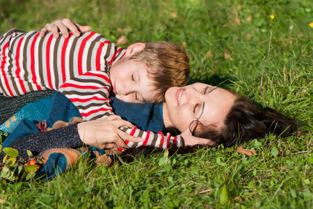 Mother and son laying on the green grass