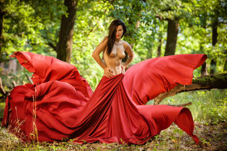 Graceful nude female folded in red silk shawl outdoors