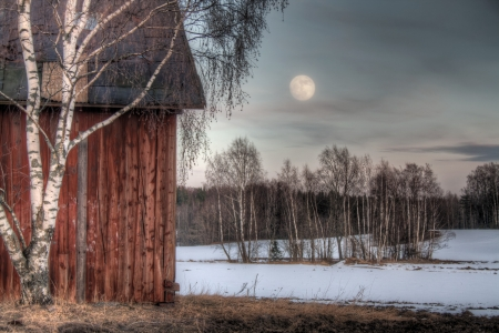 Old red barn in a countryside landscape with full moon