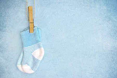 Blue baby socks on a textured rustic background with copy space