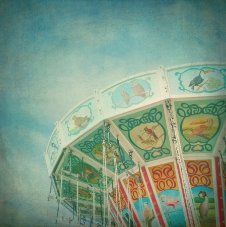 Closeup of a colorful carousel with blue sky background, with vintage style texture editing